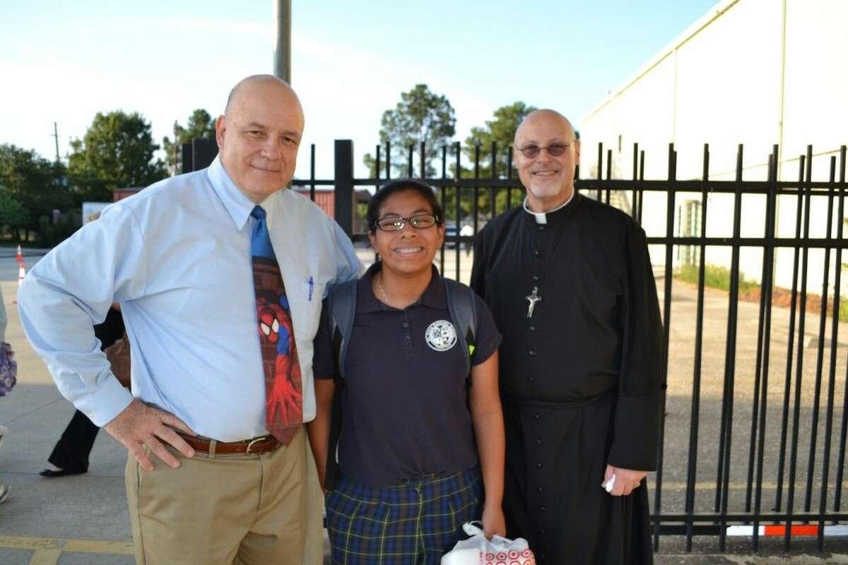 Principal Joe Noonan and the Rev. Thomas Hopper welcome 7th grader Olivia Shadick.