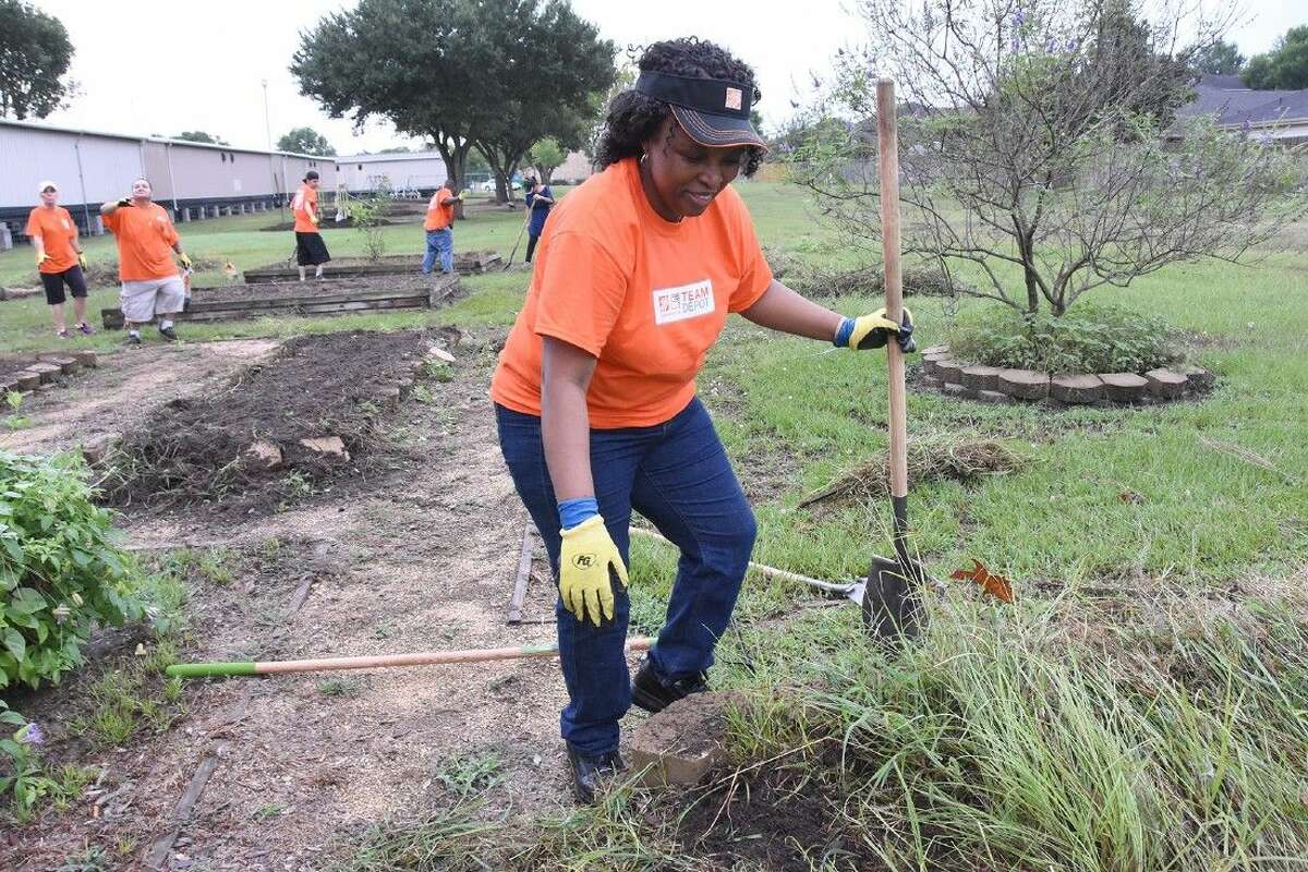 Volunteer Namagosi Mukuluatende uproots weeds from flower beds in the rear property of Francone Elementary School.