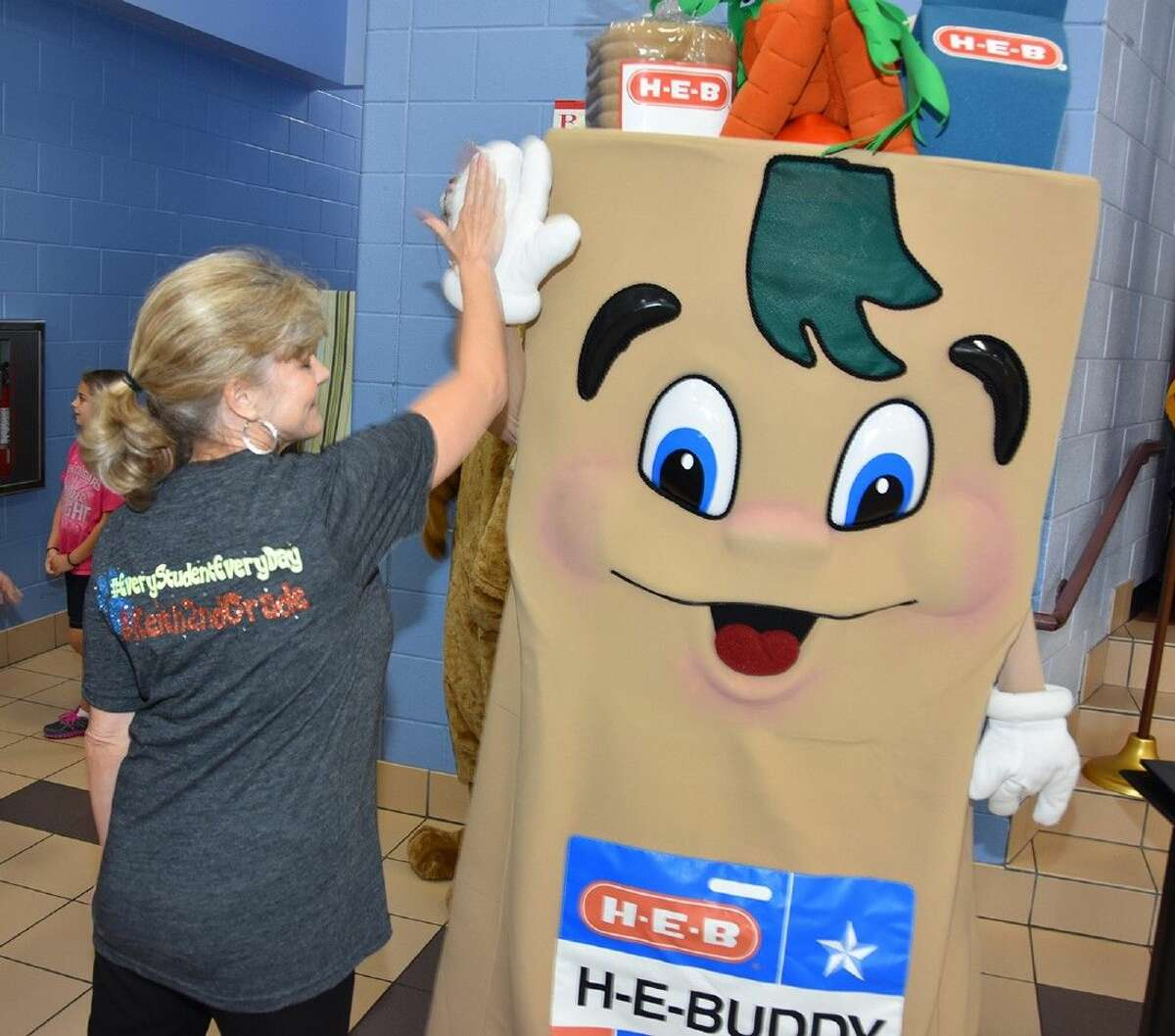 Sherry Whitmire, Keith second-grade teacher, gives a high-five to H-E-Buddy during the Adopt-a-School celebration.
