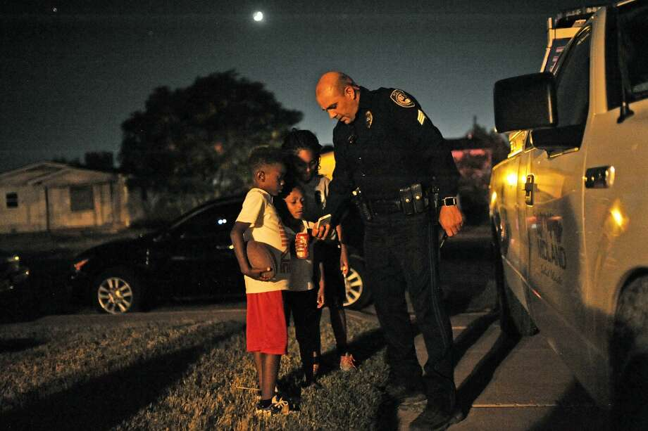Midland Police Sgt. Jimmy Young shows a picture of his wife to Jordan McGowan, R'Leighya Taylor, and Na'Mor Goodley during National Night Out on Tuesday, Oct. 4, 2016.  James Durbin/Reporter-Telegram Photo: James Durbin