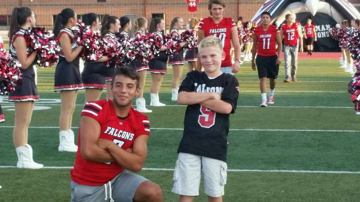 Huffman quarterback Cody Gaitan poses with a young fan during Wednesday night's Meet the Falcons event at Falcon Stadium.