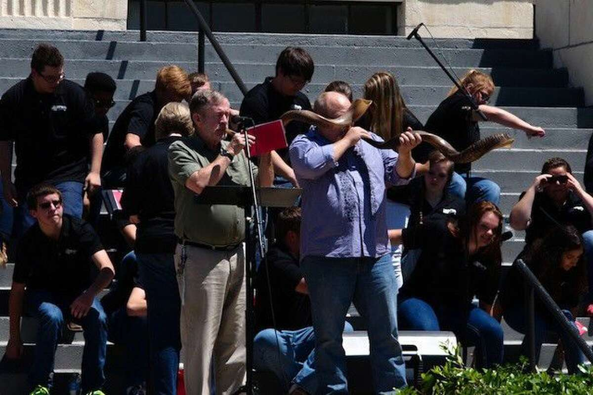 Rev. Philip Missick blows the shofar for a call to prayer on the courthouse steps in Liberty, Texas for the National Day of Prayer, May 5, 2016.