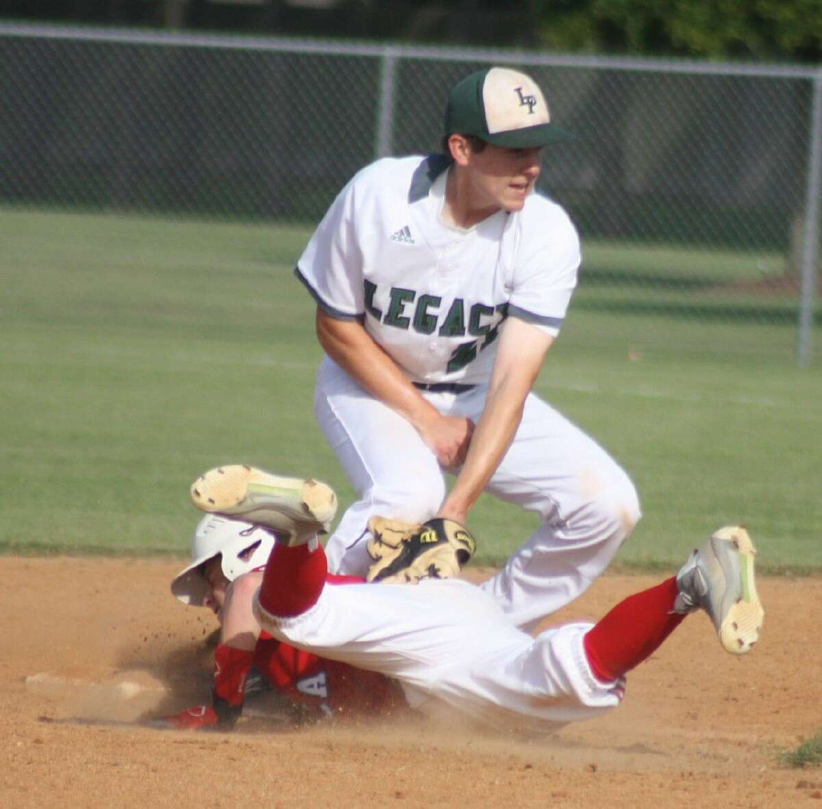 FBCA's Zach Dillard dives safely back into the second-base bag during fourth-inning action Thursday. He later scored to make it 4-0.