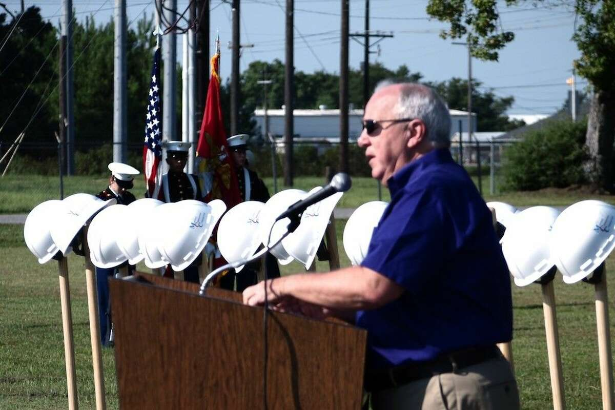 Dayton ISD Board President Larry Wadzeck speaks at the ceremonial ground breaking for the new construction at Woodrow Wilson Junior High while the high school MJROTC prepares to present the colors, Aug. 27, 2015.