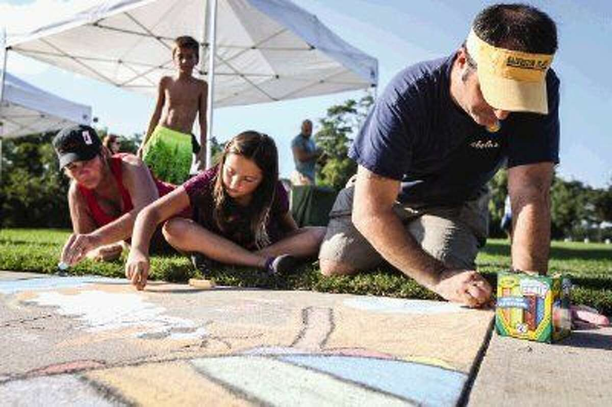The Woodlands residents Craig and Heidi Curtis and their daughter Autumn, 9, compete in the 4th Annual Family Sidewalk Chalk Competition on Sunday, Sept. 21, 2014, at Northshore Park in The Woodlands.