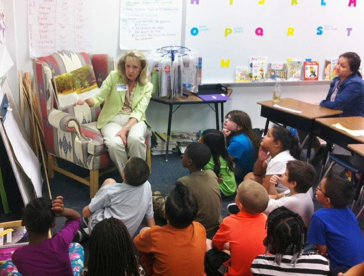 Lion Helen Thornton (seated), third vice president of the Conroe Noon Lions Club, reads to students at Reaves Elementary School last week as part of the club's