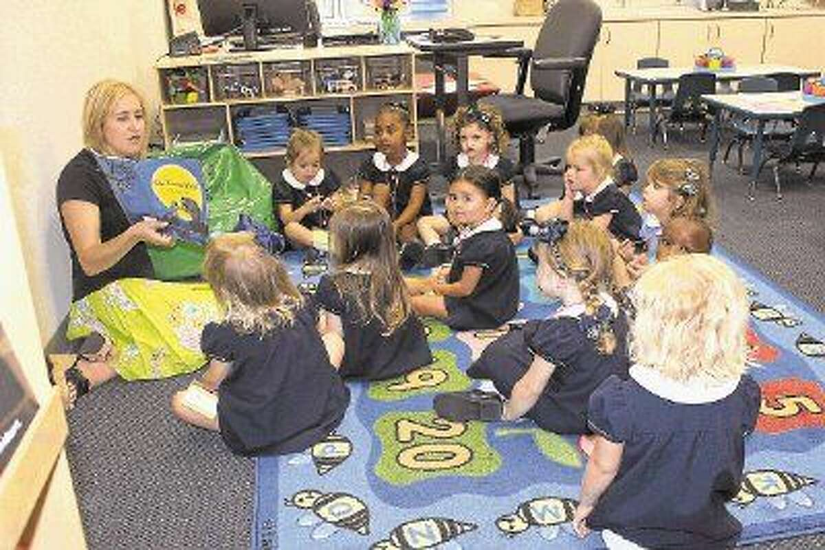 Maria Castleberry, reads to PreK 3 Petite Heart students on their first day of school at Duchesne Academy of the Sacred Heart.