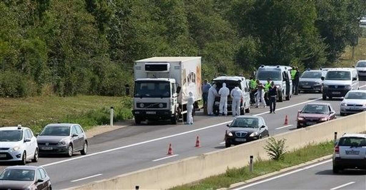 Police stands near a truck that stands on the shoulder of the highway A4 near Parndorf south of Vienna, Austria, Thursday. At least 20 migrants were found dead in the truck parked on the Austrian highway leading from the Hungarian border, police said.