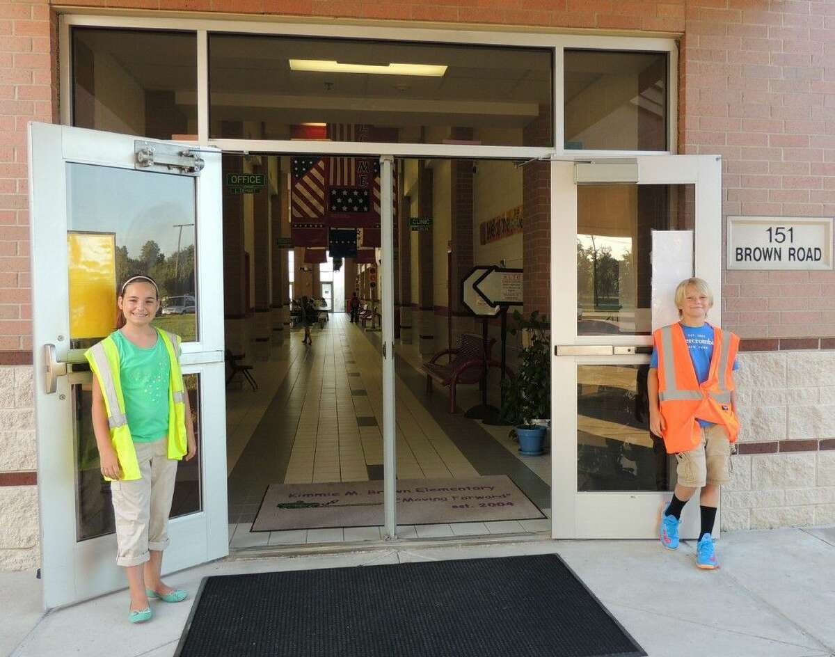 Kyndall Kelley and Ashton Garner hold the door open for staff and students.