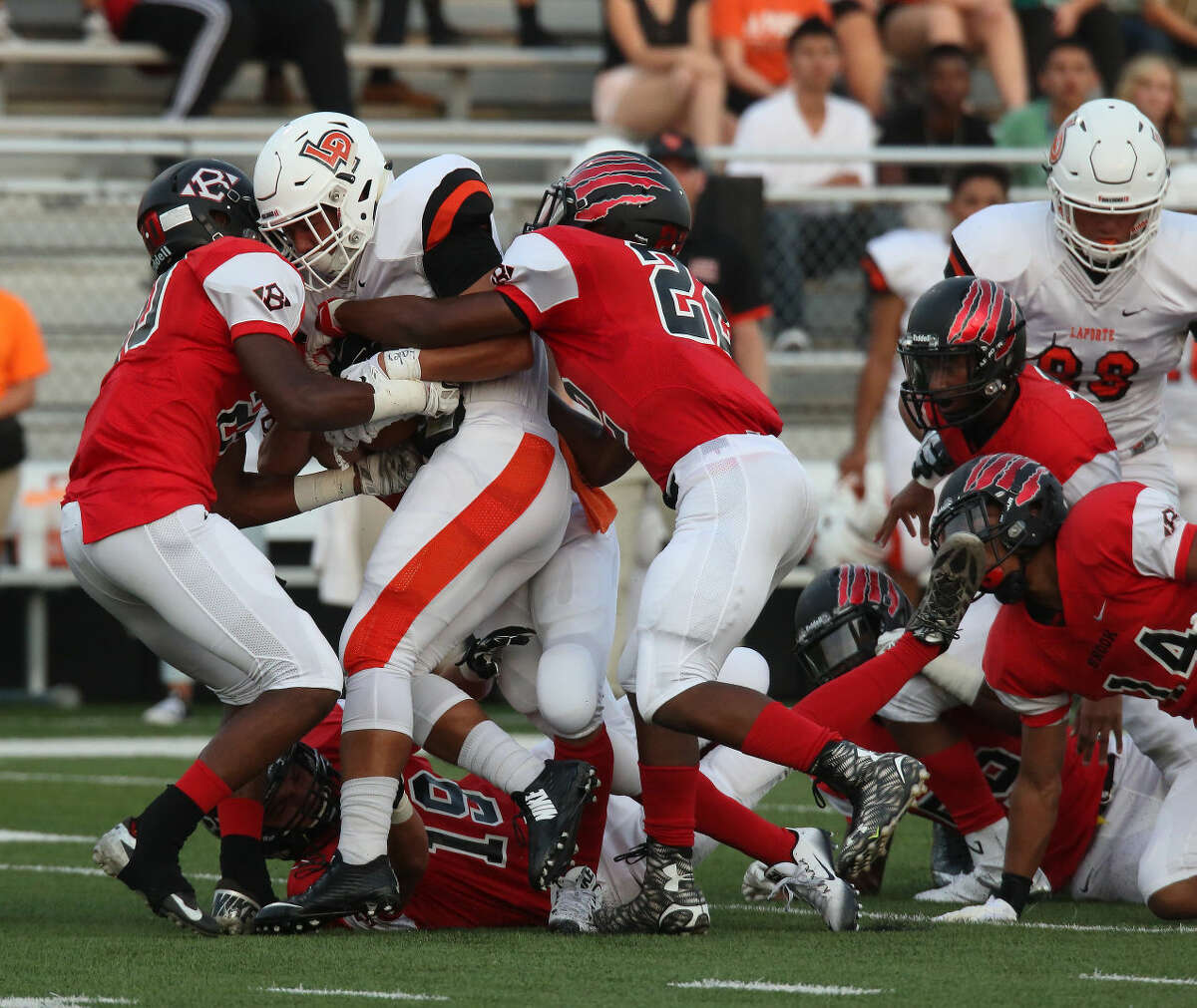 Clear Brook's Tywon Mackey (20) and Khalil Guinn (22) surround the La Porte ball carrier.