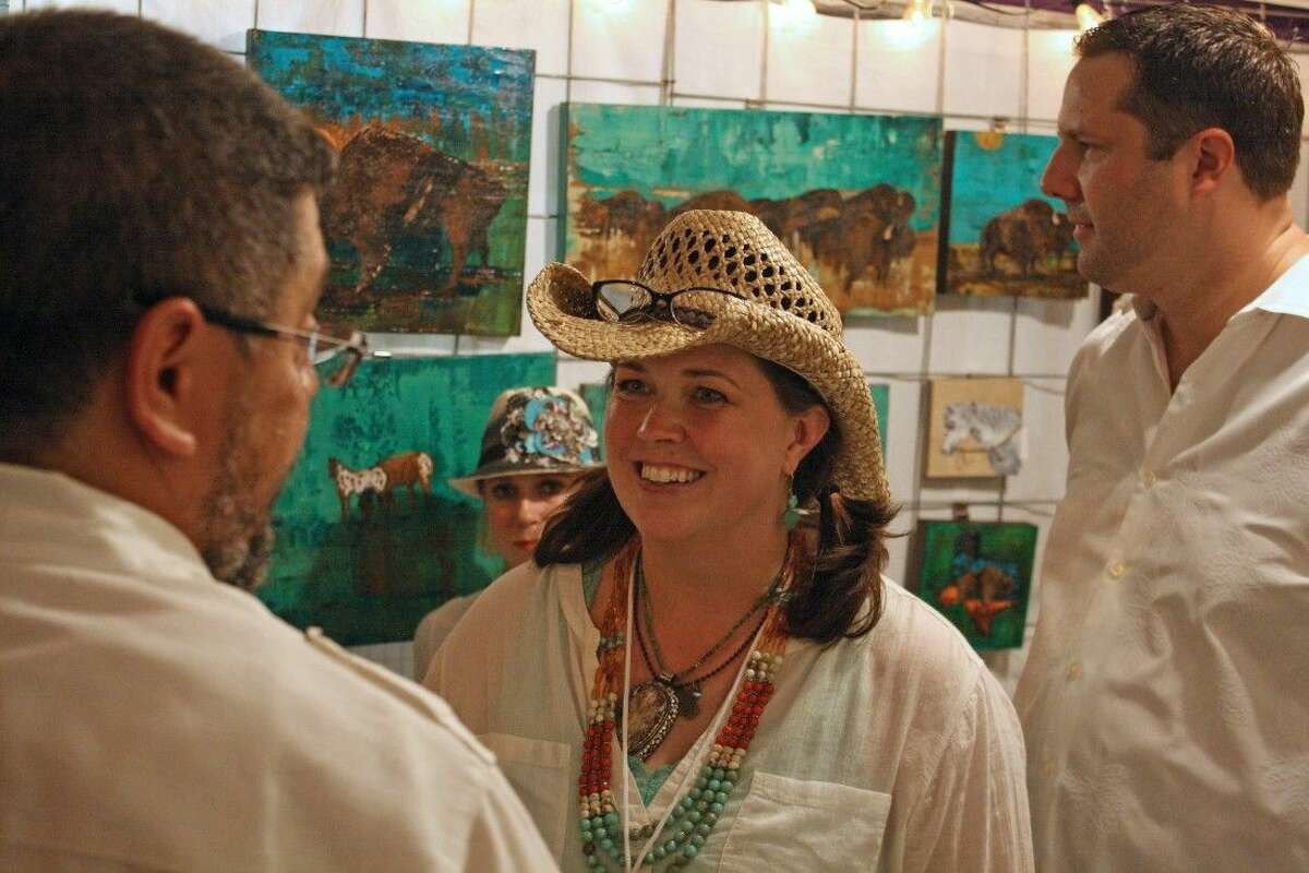 Artist Holly Nowak with a customer at White Linen Night in the Heights, snapped by Darlene Besier. Nowak will be attending the September day show of First Saturday Arts Market
