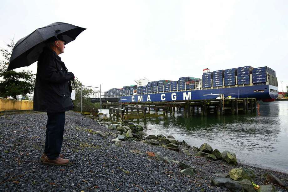John Jenkins watches the CMA CGM Benjamin Franklin container ship as it's towed to a Seattle terminal. Imports jumped 1.2 percent to $228.6 billion, while exports were up 0.8 percent to $187.9 billion, the fourth straight monthly increase and the highest level in 13 months. Photo: Genna Martin /Associated Press / seattlepi.com