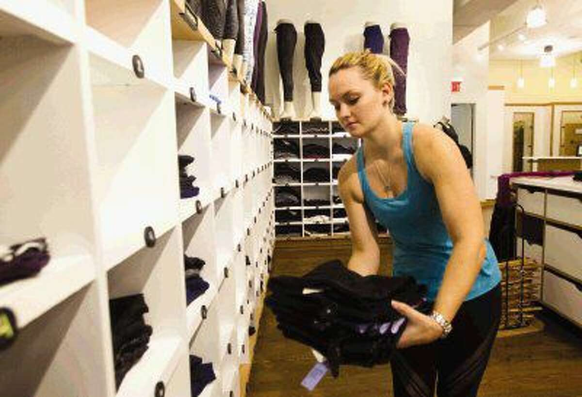 Kimberly Robertson restocks pants in the newly renovated Lululemon Athletica at Market Street in The Woodlands.