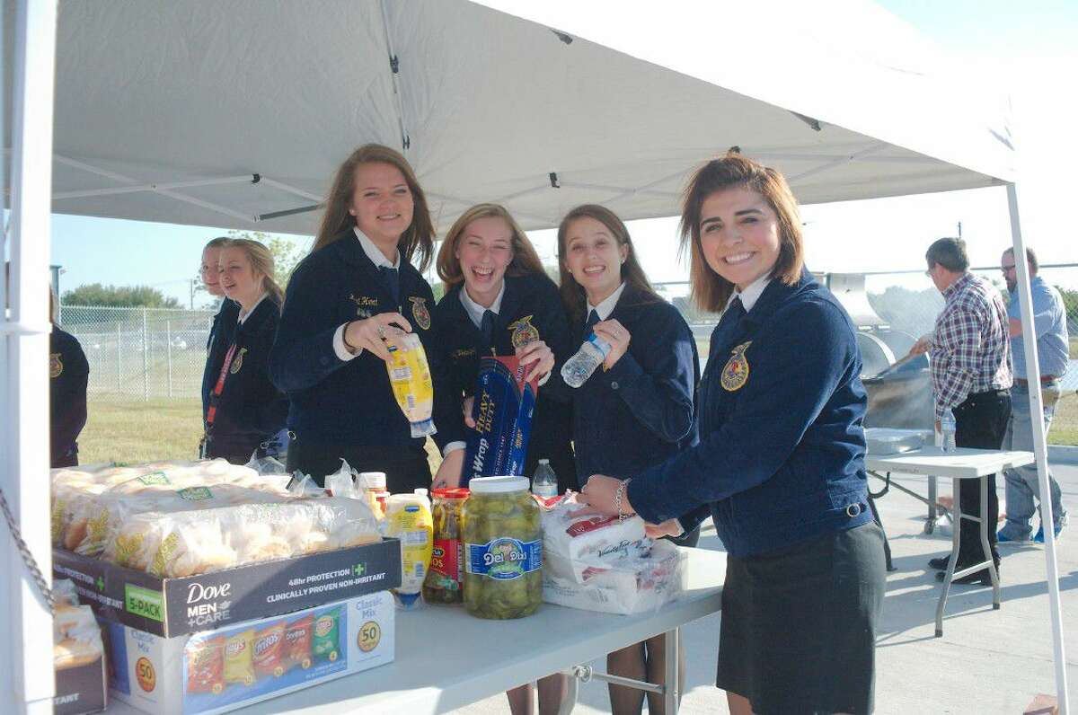 FFA students Lexi Herd, Sidney Velasquez, Bailey Heausler and Ally Humphrey serve refreshments to visitors during the grand opening of the Clear Creek ISD East Agriculture Center grand opening Tuesday, May 3.