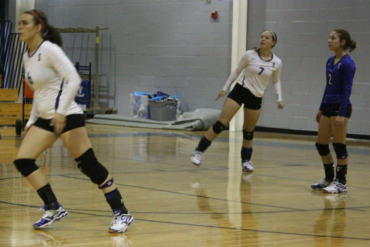 Destiny Howard (6), Shelby Brawner (7) move into positions for an incoming ball while Emily Brawner (2) holds her spot.
