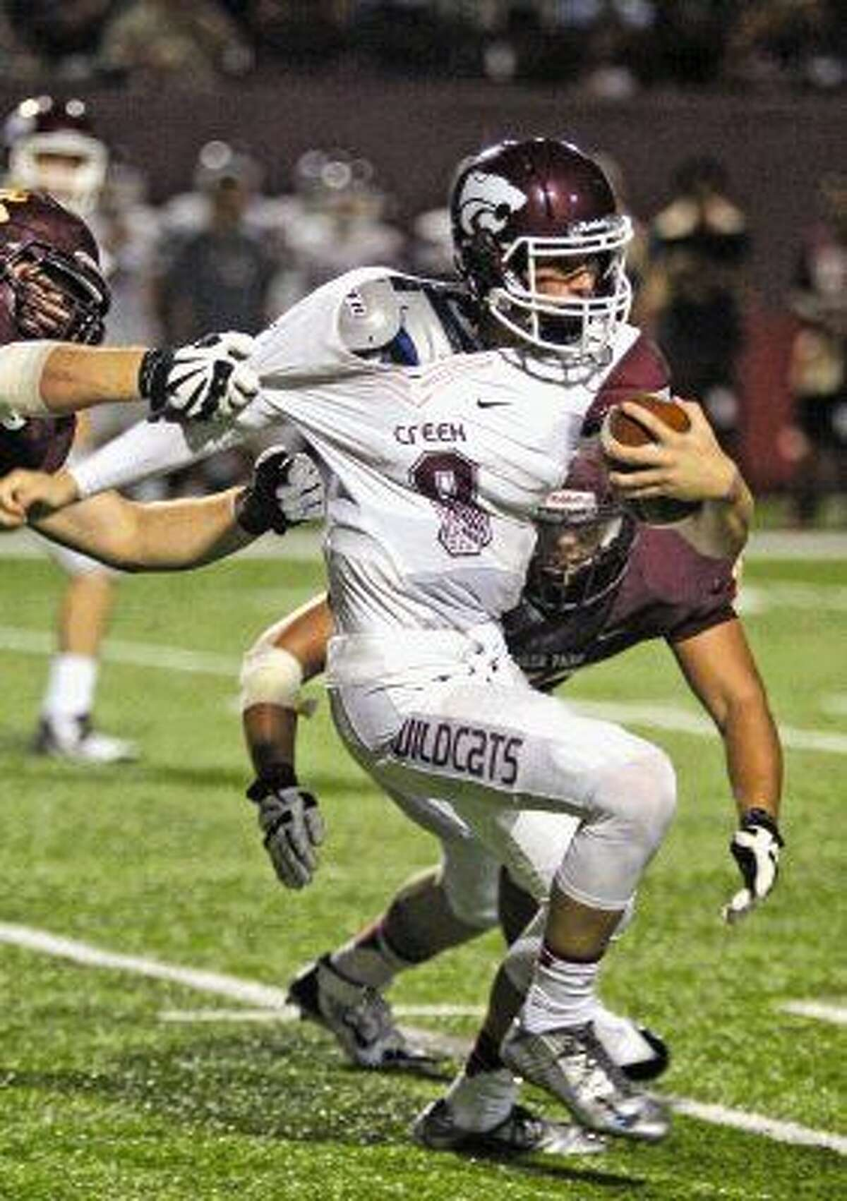 Photo by Kar B Hlava/Clear Creek quarterback Chase Hildreth gets held back by his jersey as Deer Park players close in for the tackle Friday night.