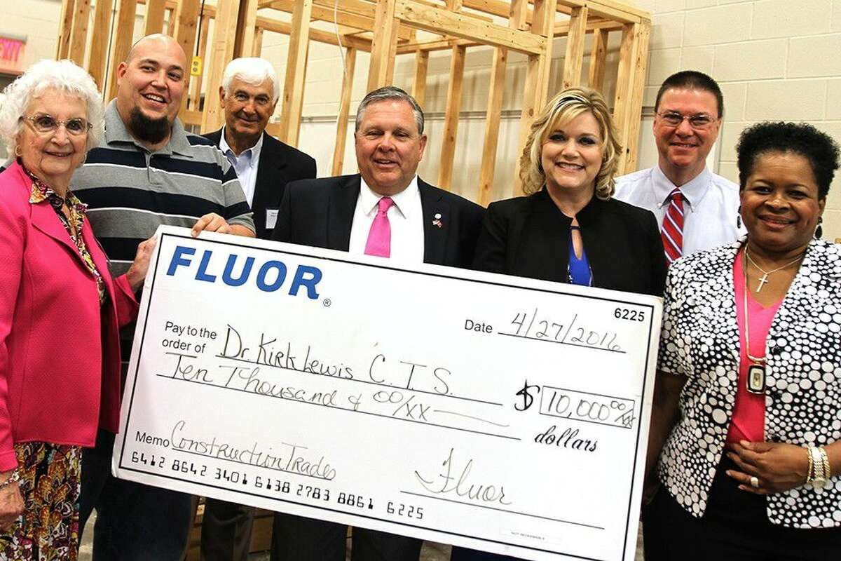 Fluor Construction presents a check for $10,000 to the Lewis Career and Technical High School at the CTE partnership breakfast. Pictured: Board of Trustee assistant secretary Nelda Sullivan, construction instructor Guadalupe Garza, board secretary Marshall Kendrick, Dan Hamrick, Fluor director of craft training and development, Superintendent Dr. DeeAnn Powell, Lewis CTHS principal Steven Fleming and Barbara Jones, Fluor senior manager of community relations and public affairs.