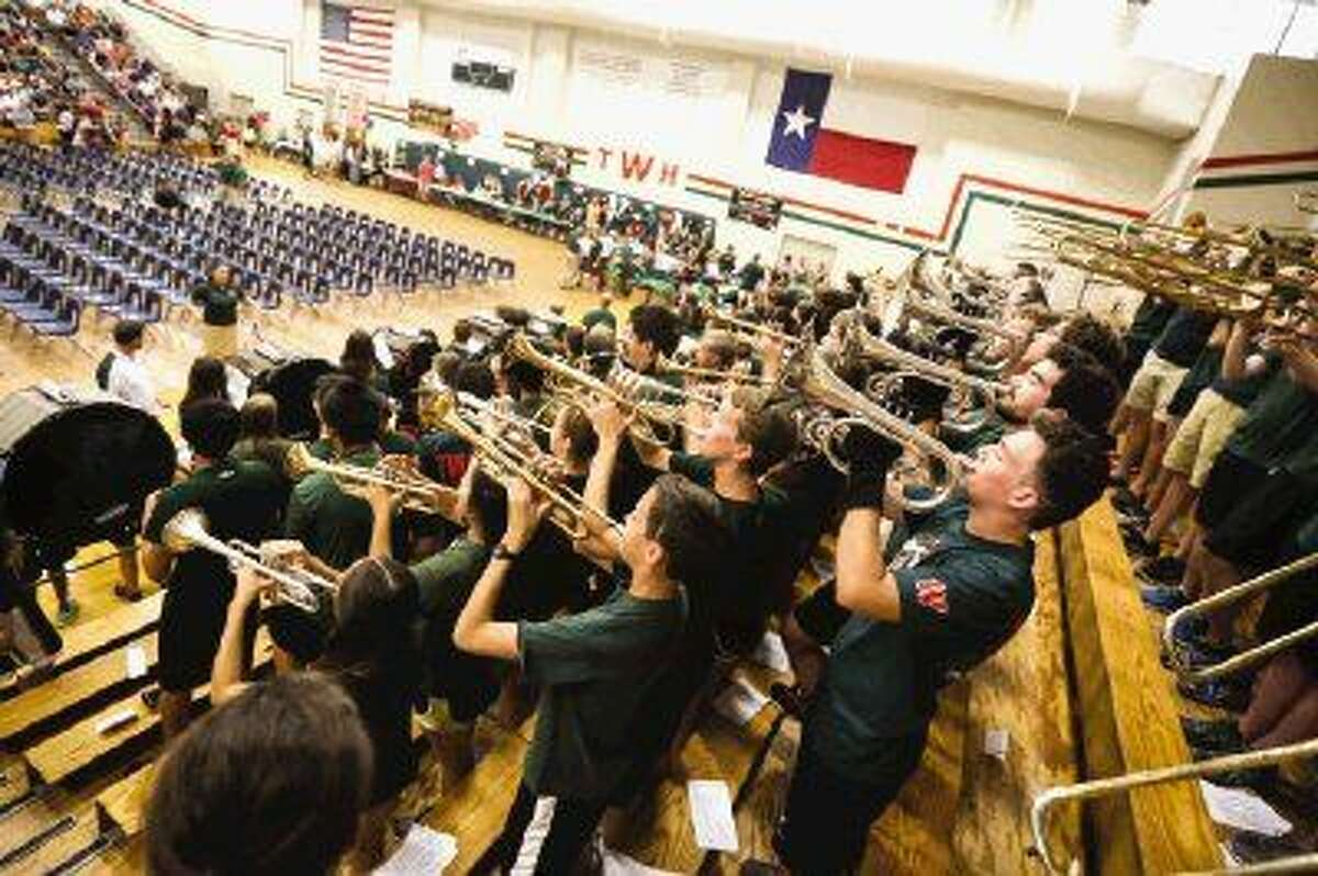 Members of The Woodlands High School band play during the Meet the Players back to school pep rally in the gym. The band has been hard at work since the beginning of August practicing this year's marching show.