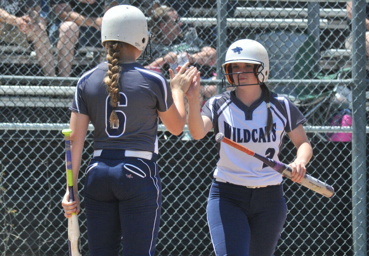 Tomball Memorial's Abbie Regitz, right, gets a high-five from Emma Guindon after scoring a run against Huntsville in a Class 5A area playoff game at Conroe High School on Saturday.