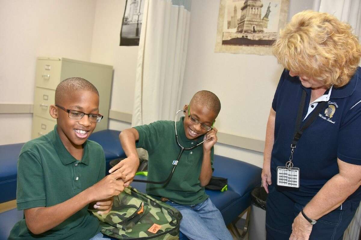 Spillane seventh-grade students Joseph and Nehemiah Dabney enjoy a fun moment on the first day of school, joined by school nurse Becky Cushen.