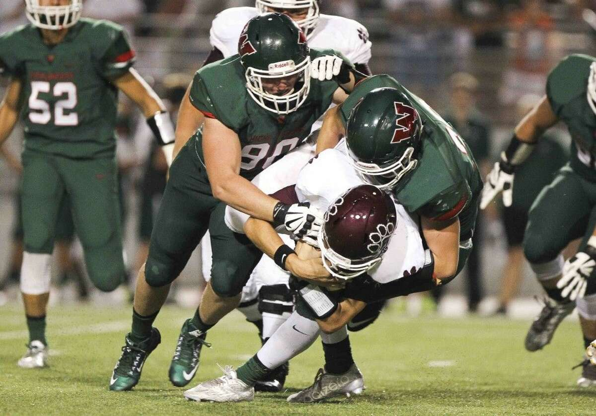 A group of Highlander defenders take down a Cy-Fair runner during a high school football game Friday.