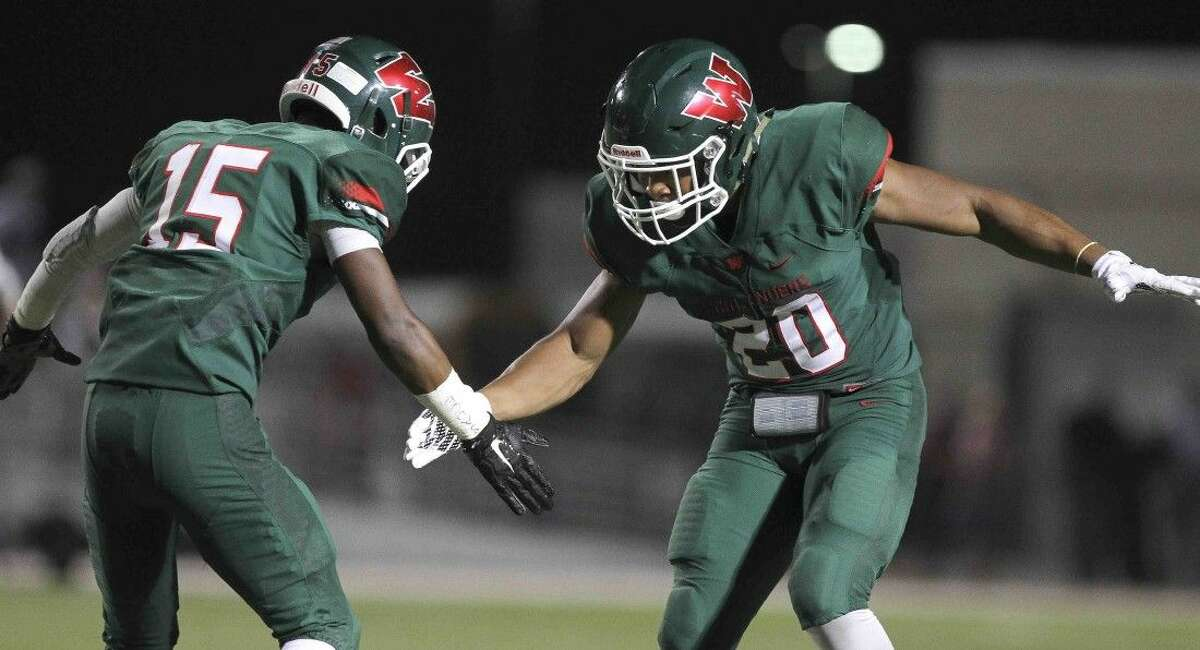 The Woodlands defensive back AJ Mason celebrates with defensive back Antoine Winfield Jr. after intercepting a pass last Friday night.
