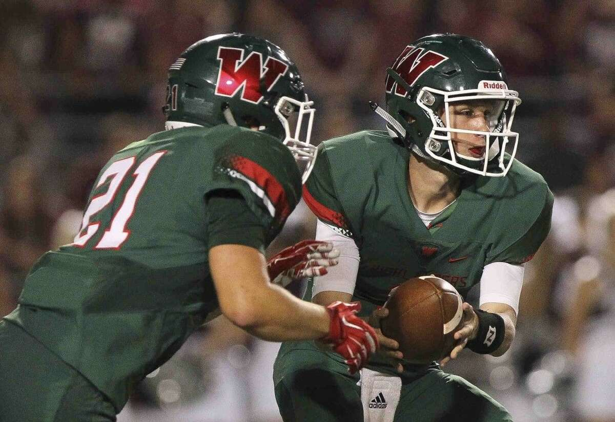 The Woodlands quarterback Eric Schmid hands the ball off to running back Lexton Trauffler during a high school football game Friday.