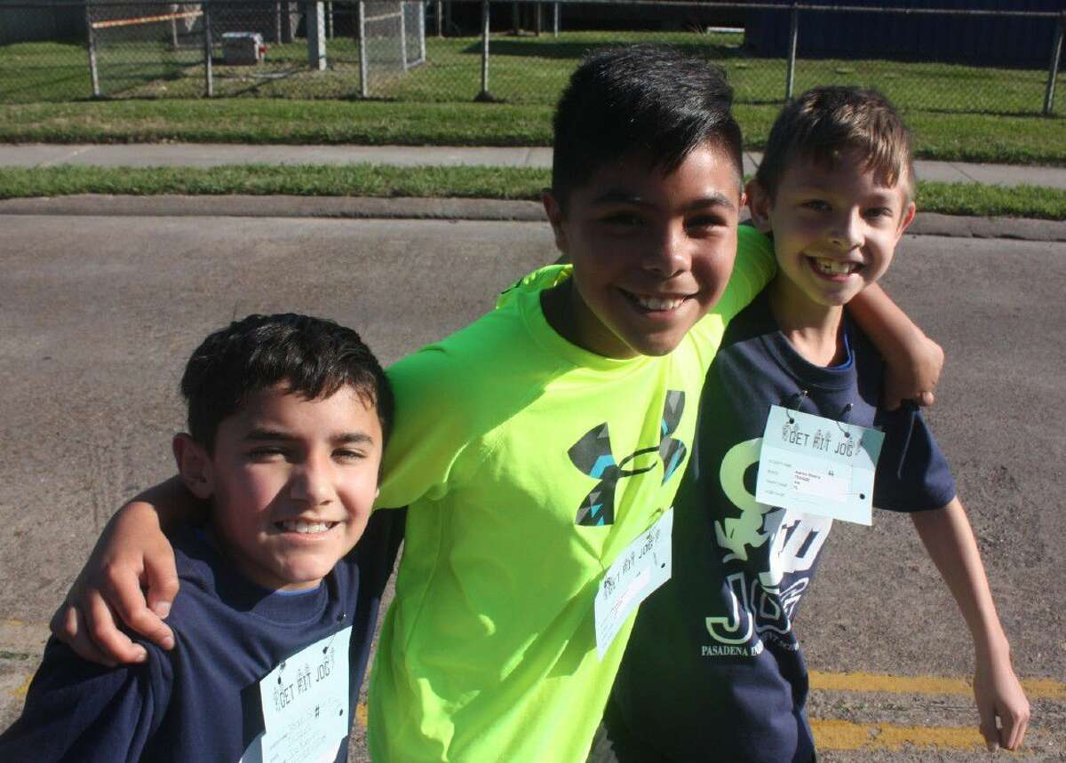 With no chance to earn a medal or ribbon and you still have over half the 2.3 mile race to complete, you do what any other fourth grader would do and that's mug for the newspaper photographer which is what these three good friends from Teague Elementary decided to do while making their way down Cherrybrook Street.