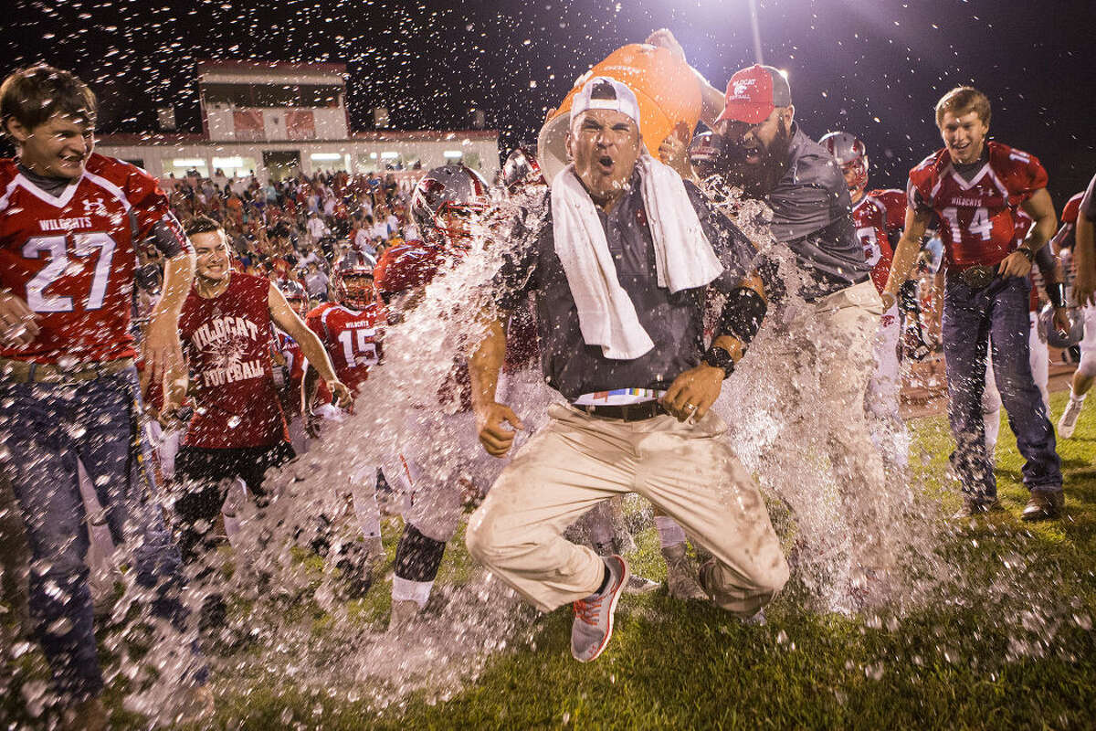 Wildcats head coach Marcus Shulz takes an ice water shower thanks to players and coaches as the final seconds tick off of Splendora's 7-0 victory over Tarkington to take the Battle of the Bell on Aug. 28, 2015, at Splendora High School.