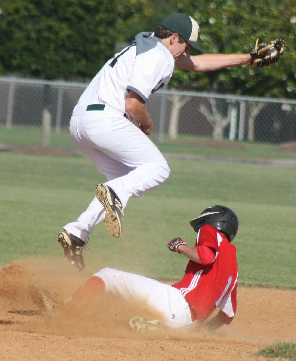 As Legacy Prepratory shortstop Ben Schardt takes a high throw, FBCA's Jake Sweeney slides into second base with a double during the bi-district game. Sweeney eventually scored what proved to be the winning run to the 7-2 victory.