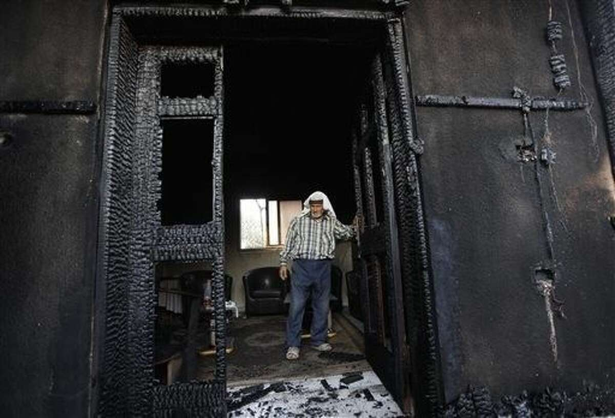 """A Palestinian inspects a house after it was torched in a suspected attack by Jewish settlers, killing an 18-month-old Palestinian child, according to a Palestinian official from the area, at Duma village near the West Bank city of Nablus. In the wake of the attack, Israeli Prime Minister Benjamin Netanyahu pledged """"zero tolerance"""" for what he called Jewish terrorism."""