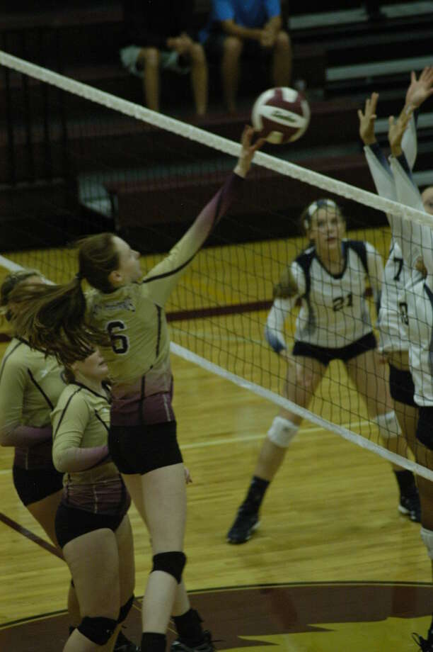 Magnolia West's Cora English (6) tips the ball over the top of the net against Tomball Memorial on Tuesday, September 23, at Magnolia West High School in a 3-1 victory. Photo By Joshua Koch/HCN