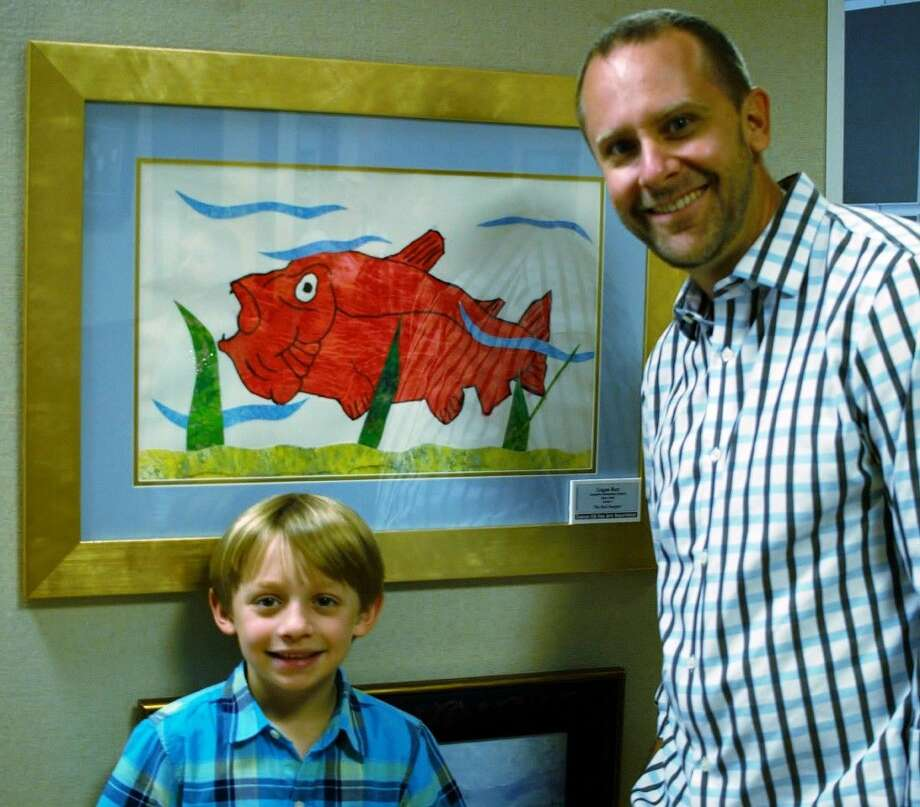 Logan Barr, a student at Deretchin Elementary is pictured with his art work and with family member Shawn Clark.