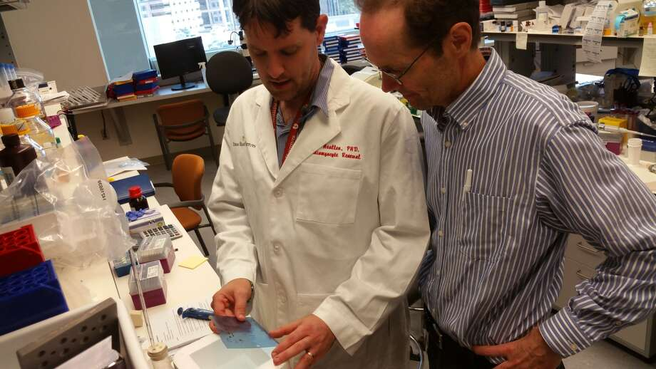 Dr. James Martin, right, discusses their work on heart regeneration with research scientist Todd Heallen at the Cardiomyocyte Renewal Laboratory at Texas Heart Institute.