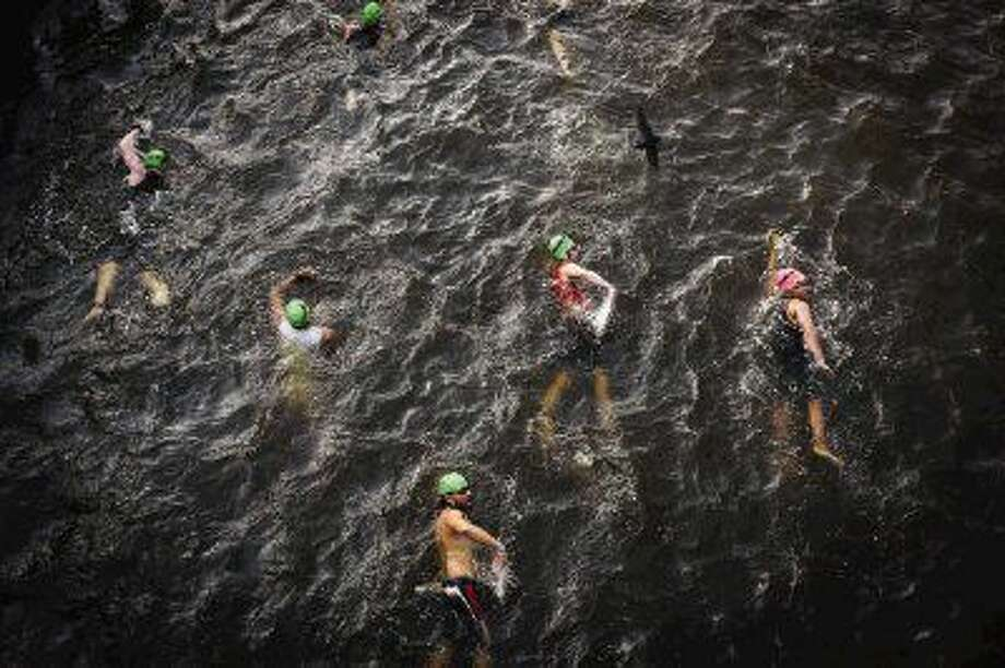 Swimmers make their way down The Woodlands Waterway during the Memorial Hermann Ironman North American Championship May 16, 2015, in The Woodlands. Ironman officials informed participants Thursday morning that the Waterway was removed from the swim route due to concerns about water quality in the canal. Swimmers now will make a 2.4-mile loop in Lake Woodlands, starting and finishing at Northshore Park, instead of completing the swim portion at Town Green Park. Photo: Michael Minasi