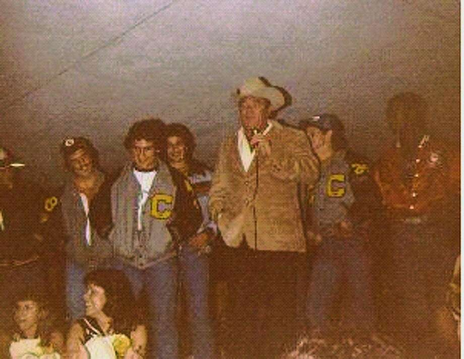Former Conroe High varsity football coach Buddy Moorhead speaks during a night time pep rally near downtown Conroe in the early 1980's. Billy Lyons is pictured with his team, second from left (in the back).