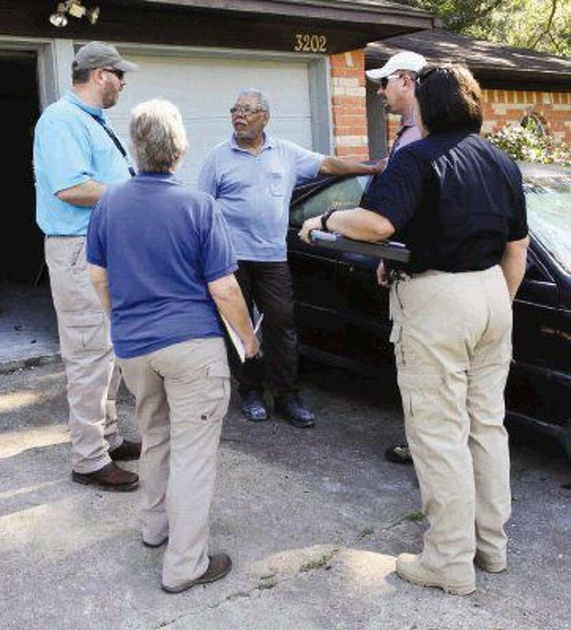 Timber Lakes Timber Ridge resident Gerson Balma speaks with officials Wednesday from FEMA, Texas Department of Emergency Management and the Small Business Association as they survey his neighborhood for flood damage.