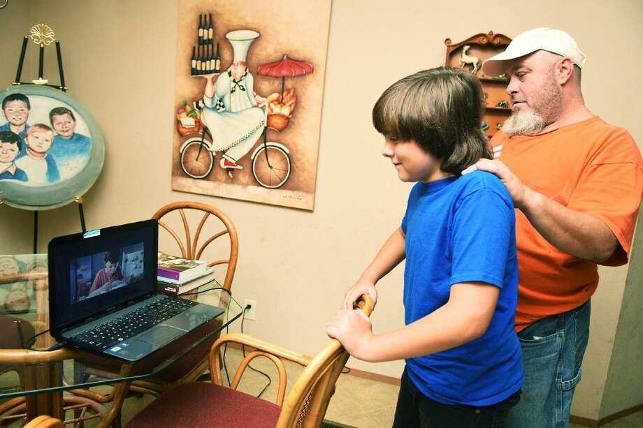 """Deke Garner and his dad Derrick Garner watches his movie """"Hellion"""" on his laptop."""