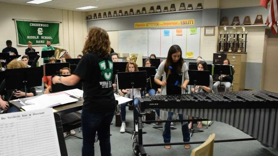 New Creekwood Middle School band director, Ariel Gammons, plays the marimba as Creekwood Middle School band director Melissa Allen directs the honors band in playing a piece commissioned to feature their new director.
