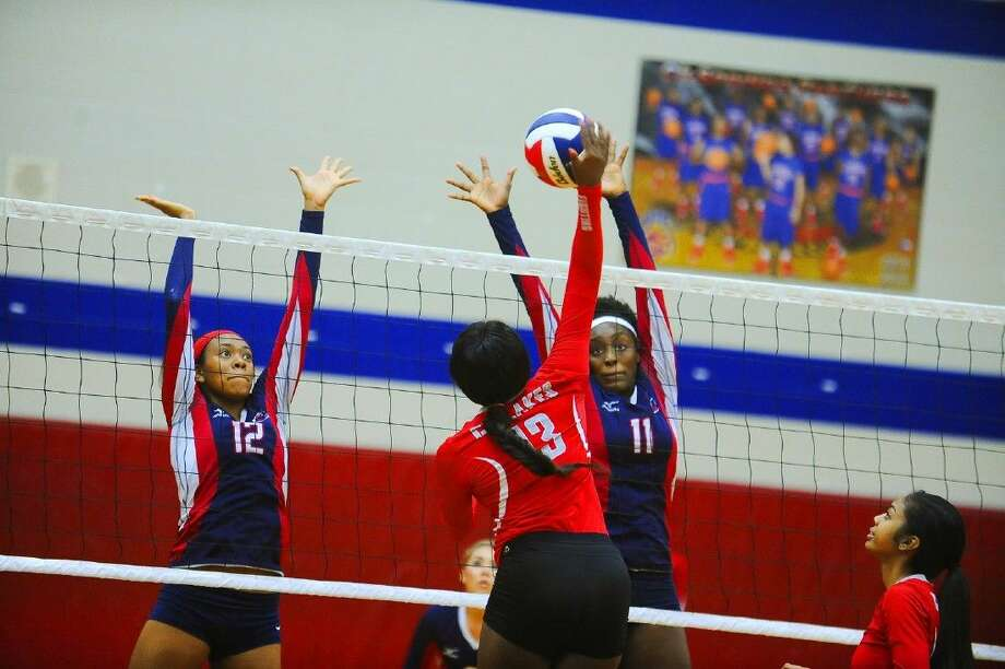 Cy Lakes' Dominique Kassim (No.13) tries to spike the ball past Shelby Jolly (No.11) and Mykayla Williams (No.12). Photo: Tony Gaines