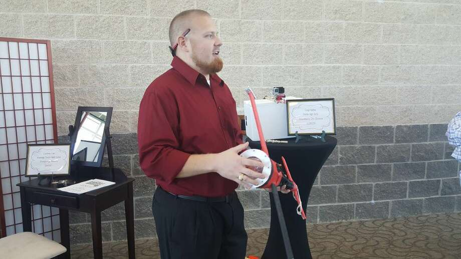 Porter High School Aerospace Engineering teacher Craig Maddux explains the paper airplane his students created with NCISD Education Foundation grant during the Breeze into Summer Luncheon at Texan Drive Stadium Friday, May 6.