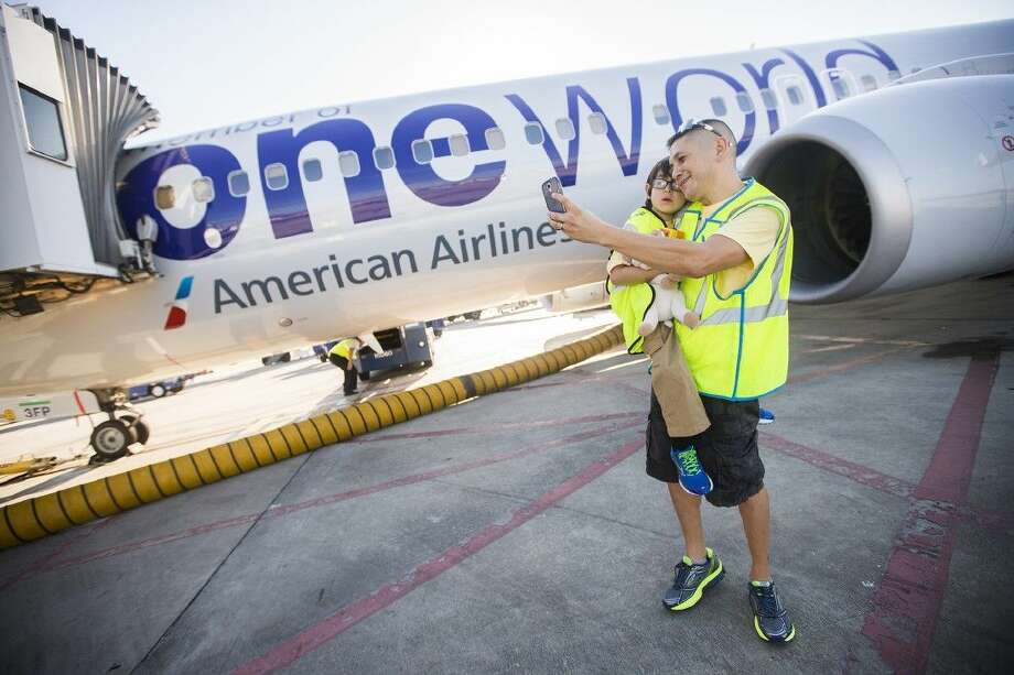 Matthew and Clemente Gonzalez take a photo as they take a tour of the tarmac during the Something mAAgic Foundation's mAAgic Flight celebration in honor of Matthew before his family departs for Orlando, Fla., on Sept. 26, 2014, at George Bush Intercontinental Airport.