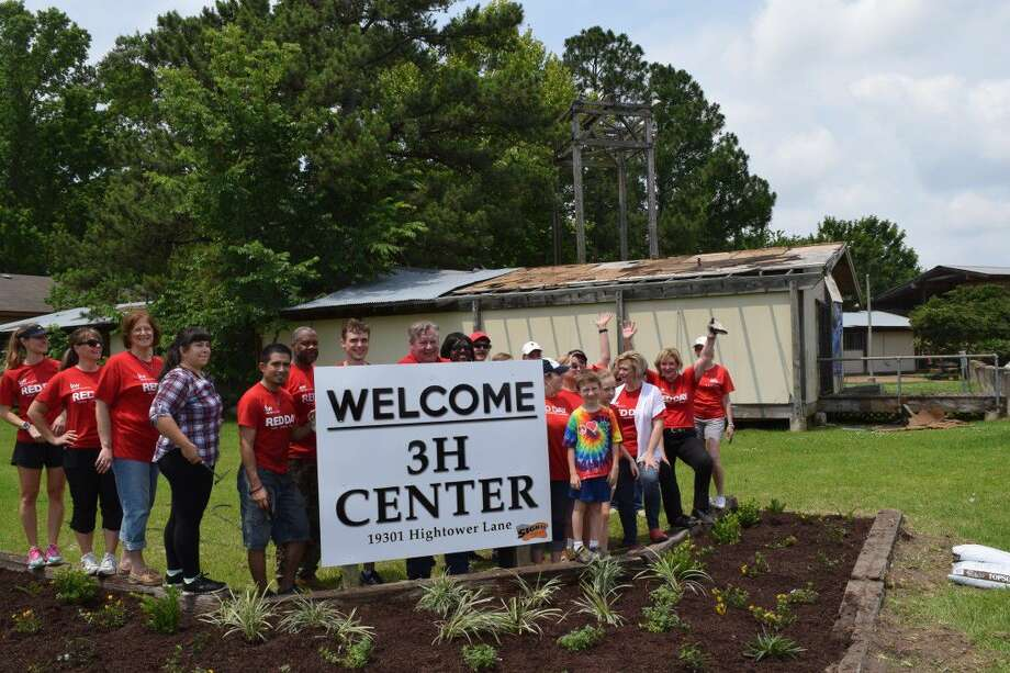 Keller Williams Northeast RED Day volunteers pose next to the plant bed and new sign they installed at Bordersville 3H Community Center in Humble during RED Day Thursday, May 12.