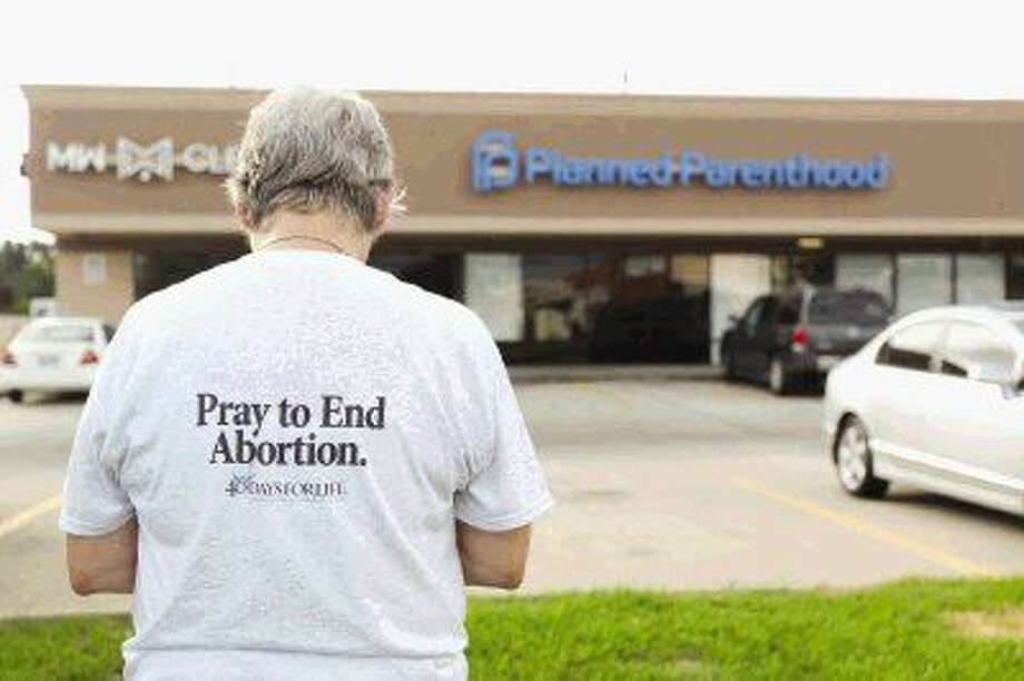 Patty Schulze, a member of Sacred Hearth Catholic Church, prays across from the Planned Parenthood location in Spring Wednesday. Catholic churches in Montgomery County are encouraging their congregation to pray to end abortion at the facility. Photo: Jason Fochtman
