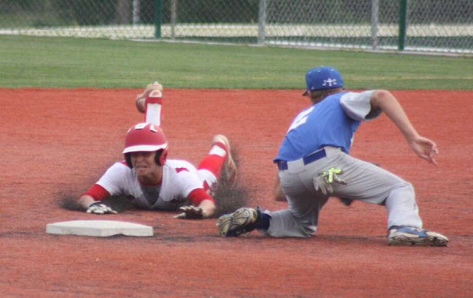 FBCA's Stephen Shaklovitz slides headfirst into second base, attempting to take advantage of one of Hallettsville Sacred Heart's errors but the Indians were able to get the ball back into the infield in time to slap the tag on the Warrior. Photo: Robert Avery
