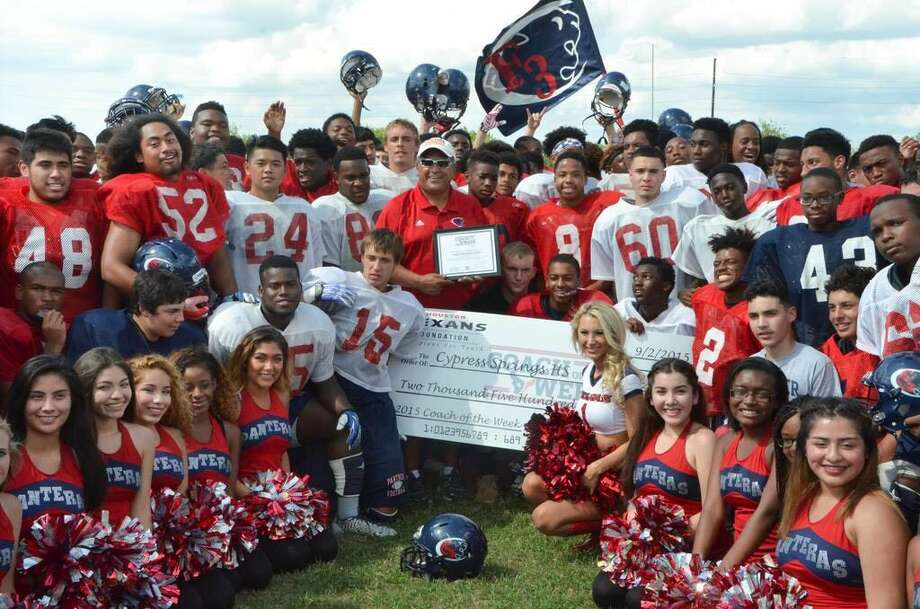 Surrounded by Panthers football players and cheerleaders and a Houston Texans cheerleaders, Cypress Springs head coach Rick Cobia accepts the Houston Texans Coach of the Week award at practice on Sept. 2.