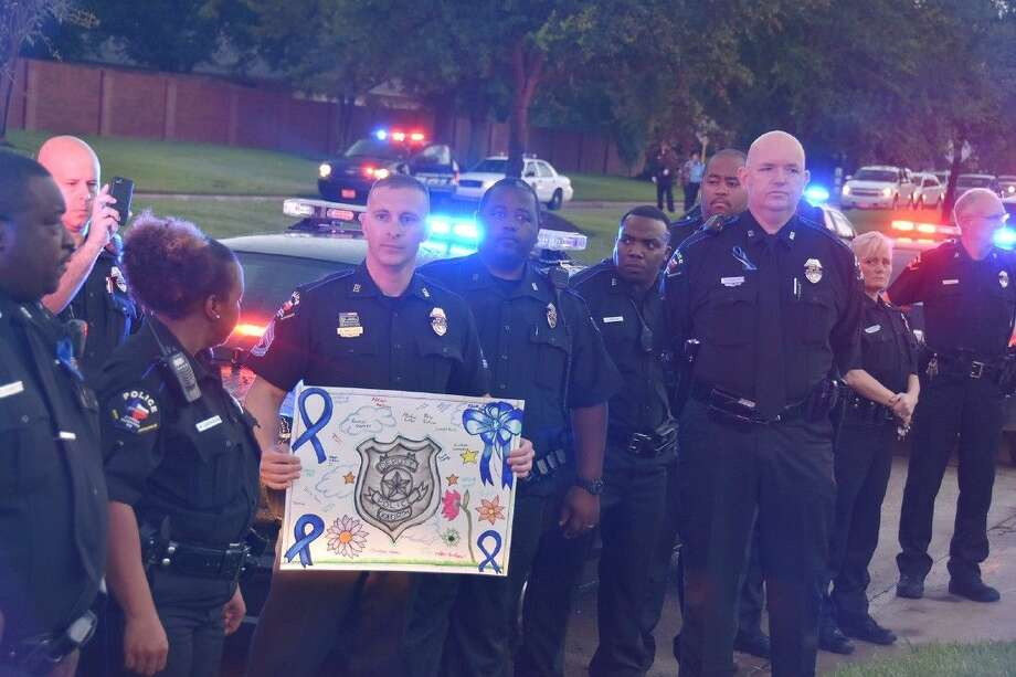 Flanked by dozens of CFISD police officers, Sgt. Shane Wallace displays tribute artwork created by Aragon Middle School students in teacher Abbey Gagnon's art class as they assemble outside of the Chevron station at Telge and West roads on Sept. 4.
