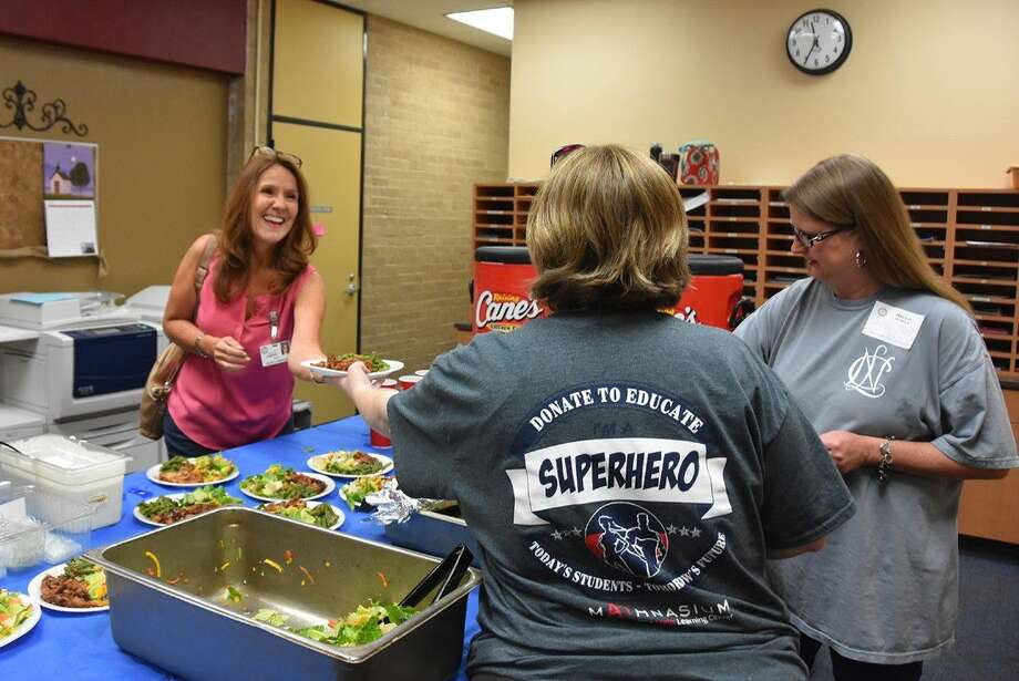 Moore Elementary School teacher Rebecca Roberts takes a plate of food from CFEF volunteers at the campus on May 10.