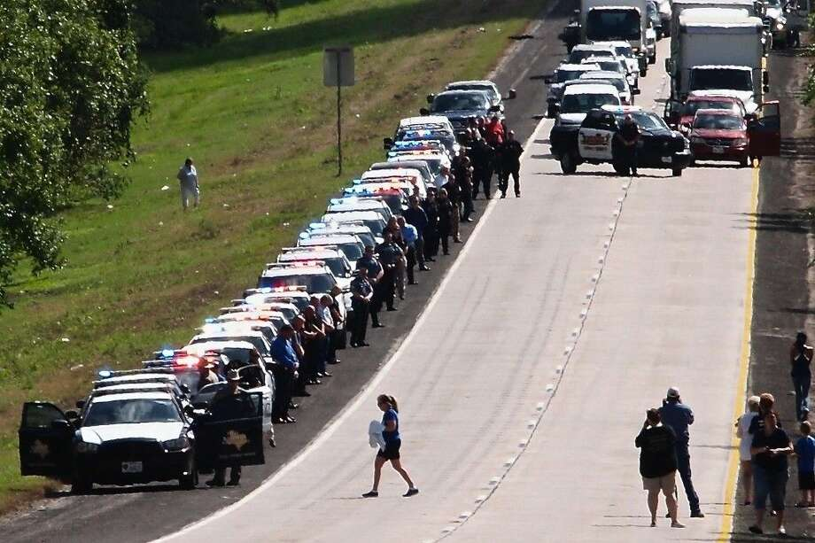 In honor of a slain Harris County deputy sheriff, peace officers working in the Liberty-Dayton area held a moment of silence on the shoulder of US 90, east of Dayton, Texas late Friday morning, Sept. 4, 2015. Photo: Casey Stinnett