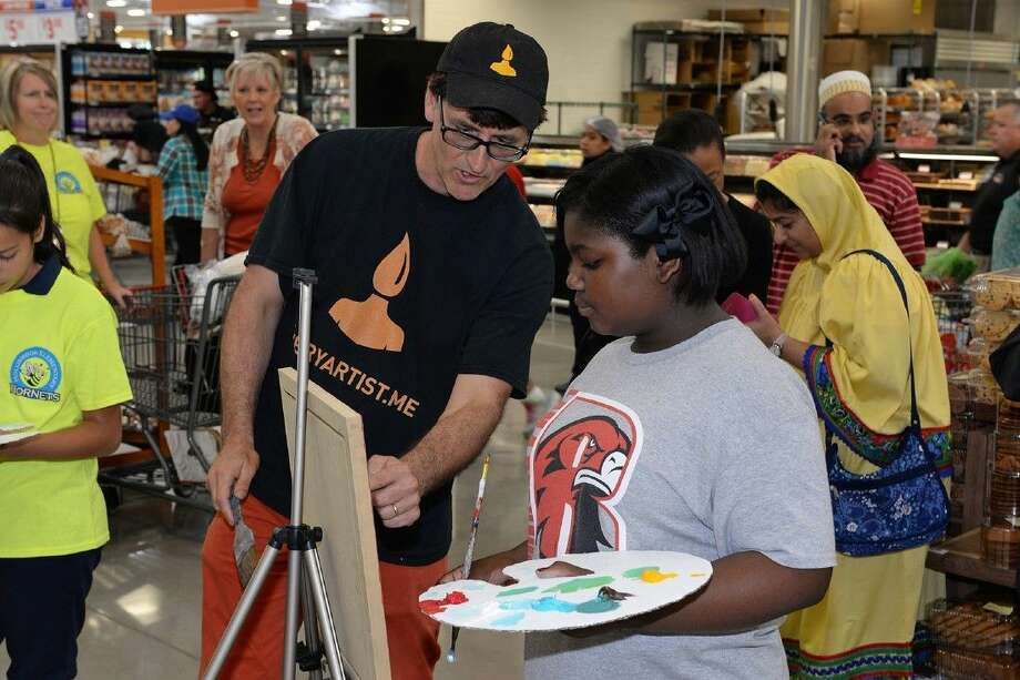Artist Brendan O'Connell guides Rennell Elementary School fifth-grade student Tralonda Washington as she creates H-E-B-themed artwork during a grand opening event at the H-E-B Market at Tuckerton store on Sept. 2.